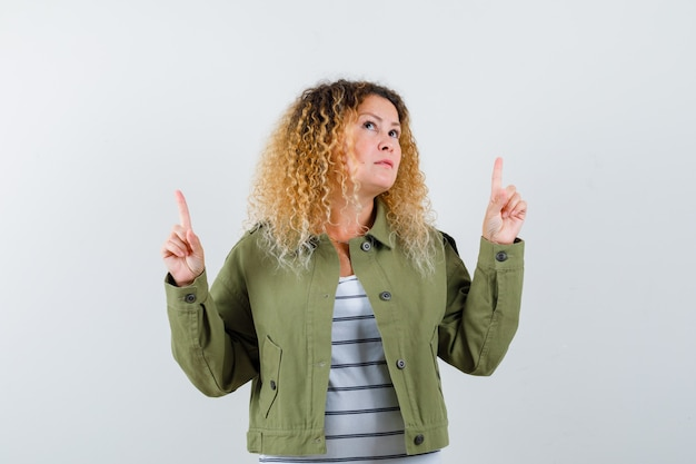 Prachtige vrouw in groen jasje, overhemd wijst en kijkt omhoog en kijkt verwonderd, vooraanzicht.