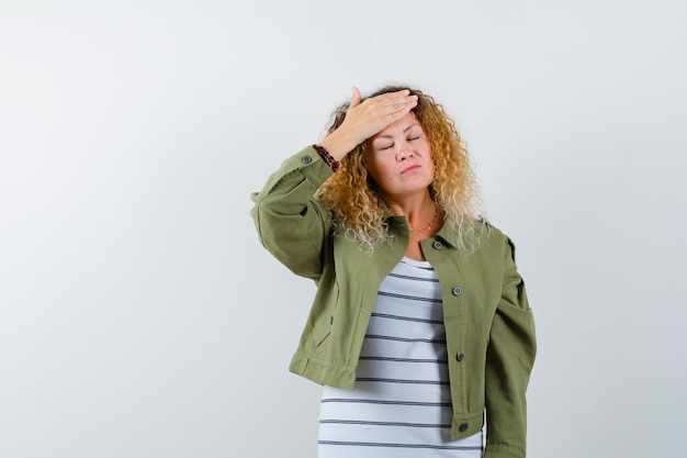 Prachtige vrouw in groen jasje, shirt met hoofdpijn en op zoek pijnlijk, vooraanzicht.