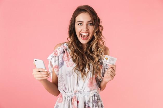 Prachtige vrouw in jurk met smartphone en creditcard, geïsoleerd op roze