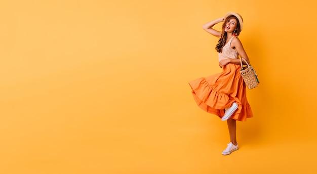 Prachtige vrouw in lange lichte rok dansen in de studio. zorgeloos geïnspireerd vrouwelijk model poseren met plezier op geel.