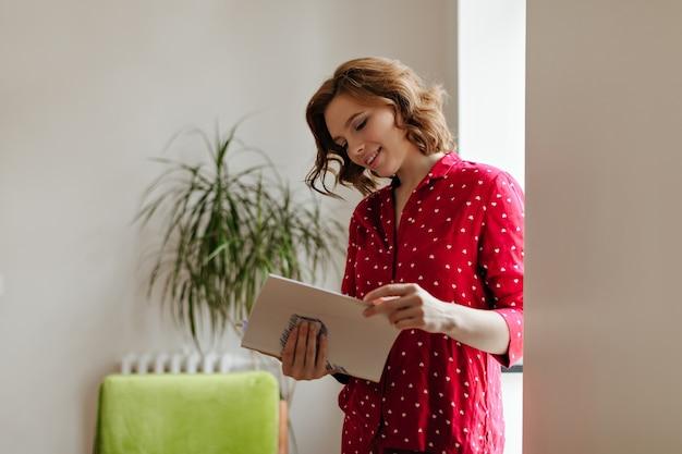 Prachtige vrouw in pyjama die met belangstelling tijdschrift leest. binnen schot van schattige krullende vrouw thuis.