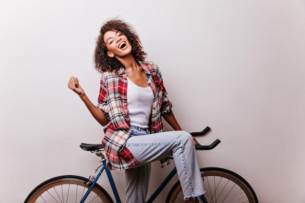 Prachtige vrouw in spijkerbroek en rood shirt poseren op de fiets. binnen schot van lachend dromerig meisje met plezier.