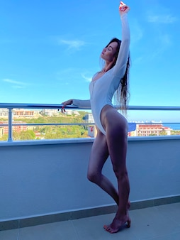 Prachtige vrouw in witte bodysuit staat op een balkon met uitzicht op zee op de achtergrond