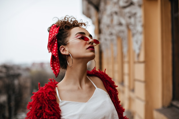 Prachtige vrouw in witte top en rode bril poseren op balkon
