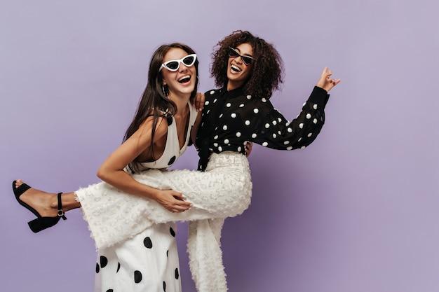 Prachtige vrouw in zwarte blouse en trendy witte broek die lacht en plezier heeft met haar vriend in zonnebril op geïsoleerde muur