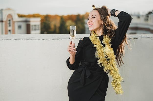 Prachtige vrouw in zwarte jurk die het uitzicht vanaf het dak bewondert