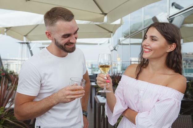 Prachtige vrouw lacht, genietend van het drinken van wijn met haar vriend in de bar op het dak
