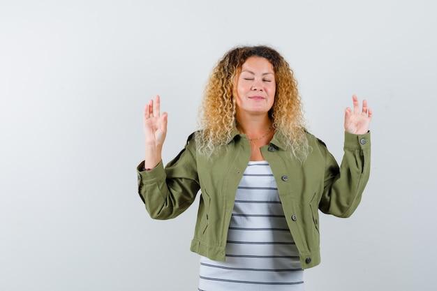 Prachtige vrouw meditatie gebaar in groen jasje, shirt tonen en vredig kijken. vooraanzicht.
