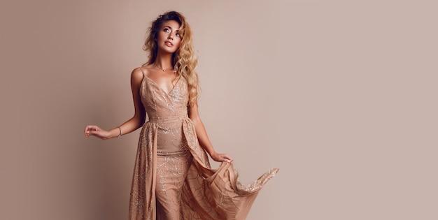 Prachtige vrouw met blond golvend haar in elegante beige jurk