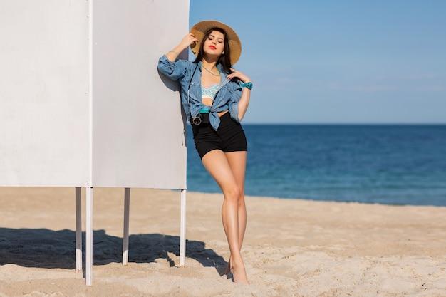 Prachtige vrouw met figuur in korte broek en strooien hoed poseren op het strand. volledige lengte.