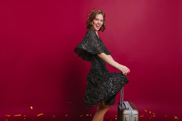 Prachtige vrouw met glanzend krullend haar dansen op feestje voor vakantie