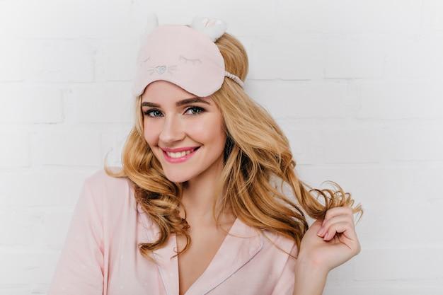 Prachtige vrouw met grote blauwe ogen poseren in de ochtend met een blije glimlach. zalig vrouwelijk model draagt zijden pyjama en roze oogmasker genietend van een nieuwe dag.