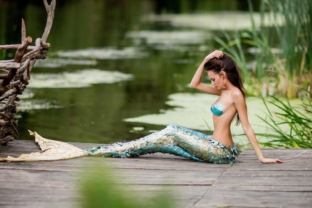 Prachtige vrouw met lang haar en gekleed als een zeemeermin zit op de brug over water