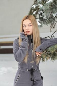 Prachtige vrouw met lang haar poseren in het bos in de winter