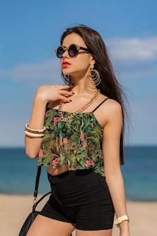 Prachtige vrouw met lange rechte haren posng op een geweldig tropisch strand.