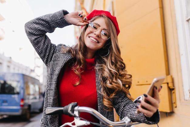 Prachtige vrouw met mooie glimlach rijden door de stad in de herfstochtend