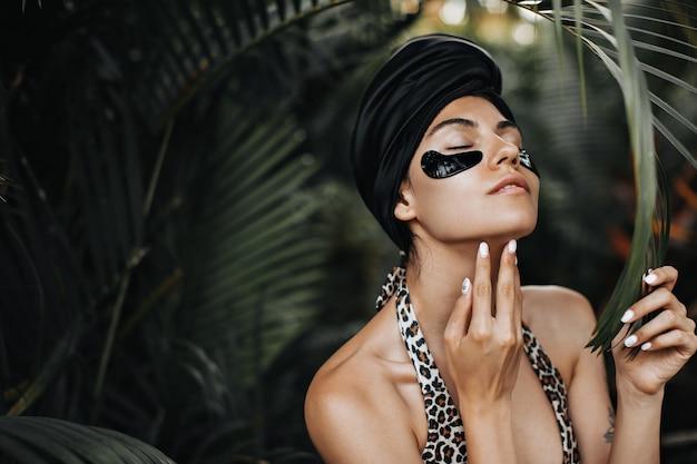 Prachtige vrouw met ooglapjes die kin aanraken. europese vrouw in zwarte tulband poseren op exotische achtergrond.
