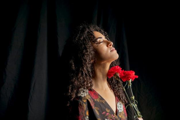 Prachtige vrouw met rode bloemen in de duisternis