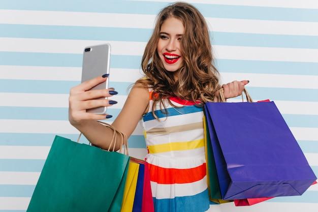 Prachtige vrouw met rode lippen selfie maken op gestreepte muur. aantrekkelijke vrouwelijke shopaholic die foto van zichzelf neemt.