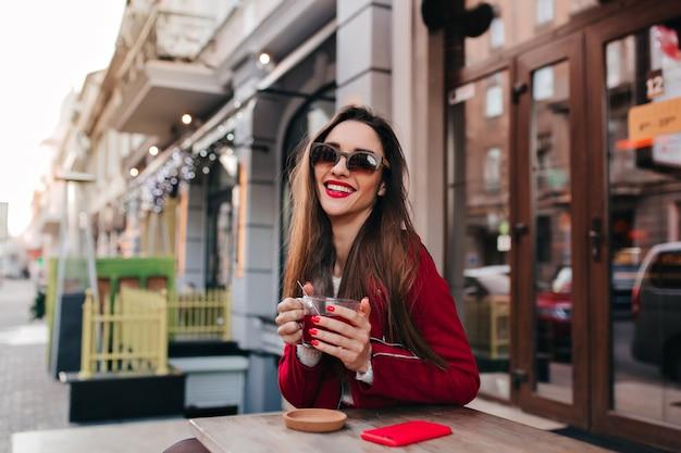 Prachtige vrouw met sluik donker haar poseren in straat café lachen
