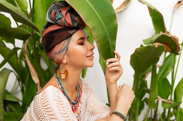 Prachtige vrouw met tulband op hoofd, kleurrijke oorbellen en boho ketting poseren
