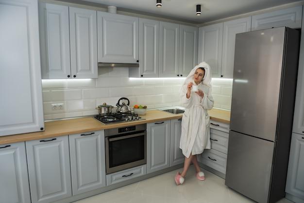 Prachtige vrouw ontspannen ochtend in de keuken en drinken genieten van koffie. comfortabel thuis vrije tijd.