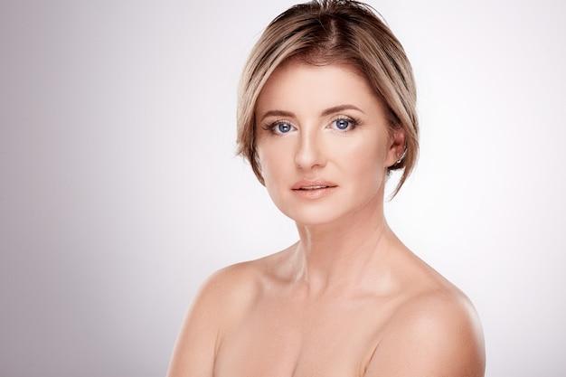 Prachtige vrouw van gemiddelde leeftijd met naakt make-up en naakte schouders poseren muur, schoonheidsfoto concept, huid en rimpels behandeling, portret.