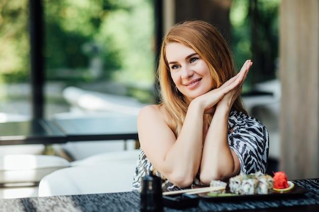 Prachtige vrouw van middelbare leeftijd zit op caféterras met een bord sushibroodjes