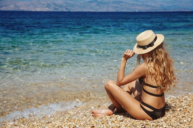 Prachtige vrouw zittend op het strand met prachtig uitzicht op zee