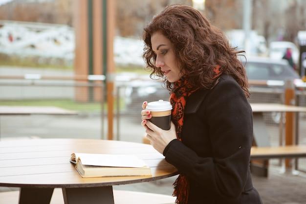 Prachtige vrouw zorgvuldig een boek lezen met een kop warme drank