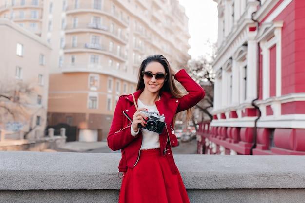 Prachtige vrouwelijke fotograaf in donkere zonnebril spelen met haar haren op stadsruimte