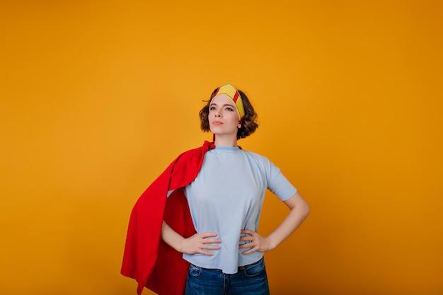 Prachtige vrouwelijke held in trendy kleding die zich voordeed op gele ruimte