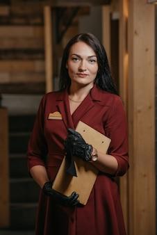 Prachtige vrouwelijke restaurantmanager in zwarte wegwerphandschoenen