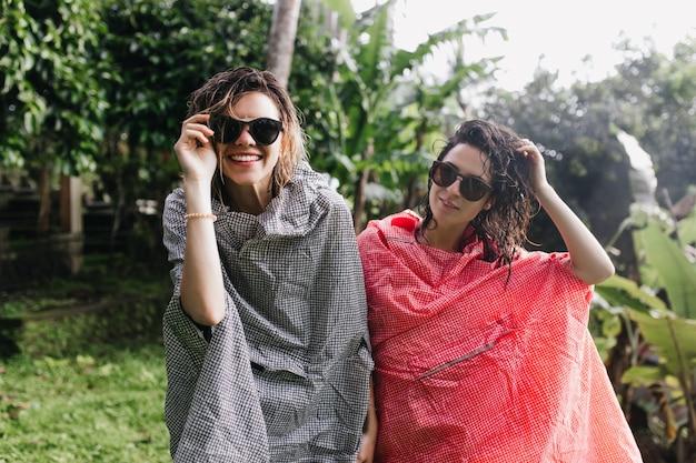 Prachtige vrouwelijke toeristen met nat haar poseren na regen. openluchtportret van glimlachende reizigers in zonnebrillen en regenjassen die zich op aard bevinden.