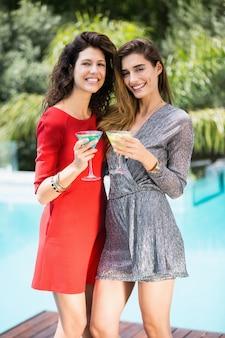 Prachtige vrouwelijke vrienden bij het zwembad
