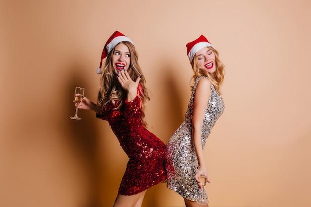 Prachtige vrouwen met krullend kapsel die voor de gek houden tijdens nieuwjaarsfotoshoot in een kamer met een licht interieur
