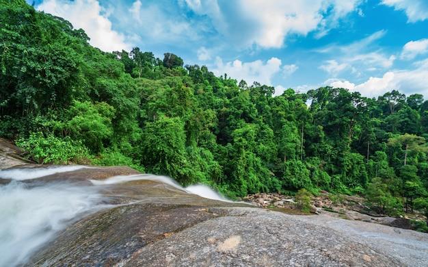 Prachtige waterval bij de berg met blauwe lucht en witte stapelwolken. waterval in tropisch groen boombos. waterval stroomt in de jungle.
