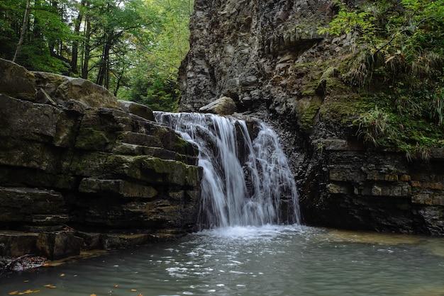 Prachtige waterval close-up. kleine bosrivier. waterstromen vallen uit de rots.