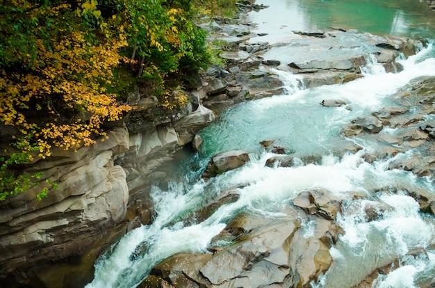 Prachtige waterval in herfst bos