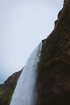 Prachtige waterval op de rotswanden gevangen in ijsland