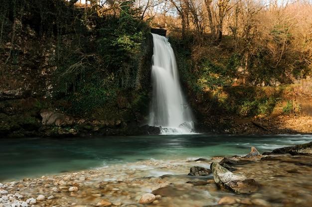 Prachtige waterval stroomt in duidelijke rivier in martvili canyon op herfstdag