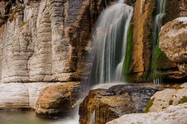 Prachtige waterval stroomt langs de hoge rots in martvili canyon