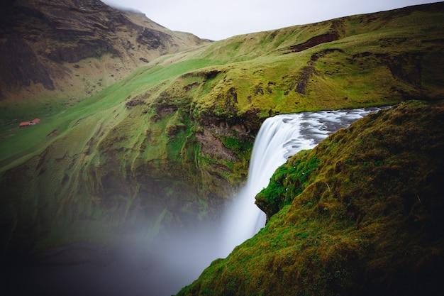 Prachtige waterval tussen groene heuvels in skogafoss, ijsland