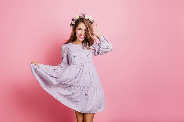 Prachtige witte vrouw in vintage paarse jurk poseren in studio