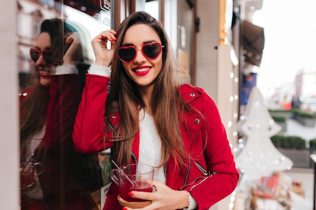 Prachtige witte vrouw met trendy make-up en manicure buiten het drinken van thee