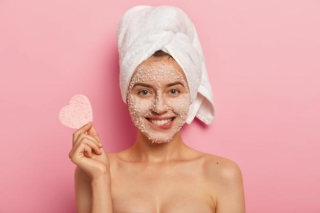 Prachtige zachte vrouw met aangename glimlach, bijt onderlip, heeft korrels zeezout aangebracht rond het gezicht, houdt cosmetische spons vast om de teint af te vegen, draagt handdoek na bad, heeft goed verzorgd lichaam