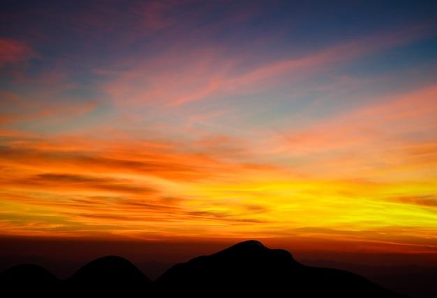 Prachtige zonsondergang en lucht, dageraad licht en shiluette bergzicht achtergrond.