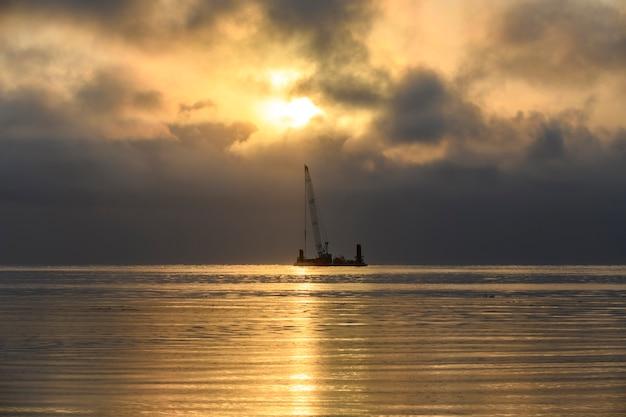Prachtige zonsondergang in de arctische zee. aak met kraan. gouden uur. bouw marine offshore werken. dambouw, kraan, schuit, baggerschip.