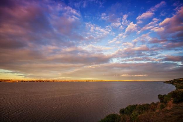 Prachtige zonsondergang op het meer met wolken en reflecties op het water