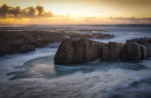 Prachtige zonsondergang over de rotsachtige zee
